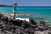 An Asian woman walks on the rocky seashore at Kiholo Bay, Big Island.