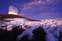 Subaru Telescope, with other observatories in background on a snowbound Mauna Kea summit at sunset