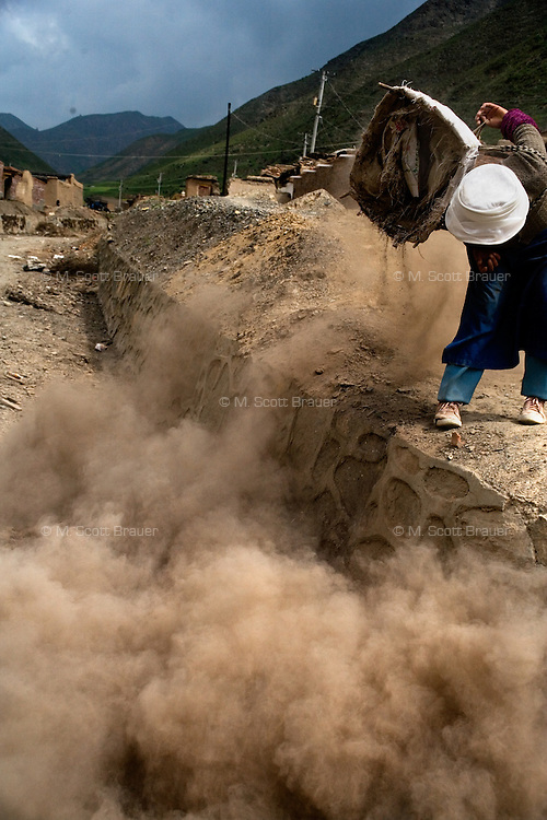 A woman dumps dirt into a garbage pit during construction work in Xiahe, Gansu, China. Xiahe, home of the Labrang Monastery, is an important site for Tibetan Buddhists.  The population of the town is divided between ethnic Tibetans, Muslims, and Han Chinese.