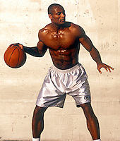 Basketball player guards the ball and looks down the court while dribbling the ball.