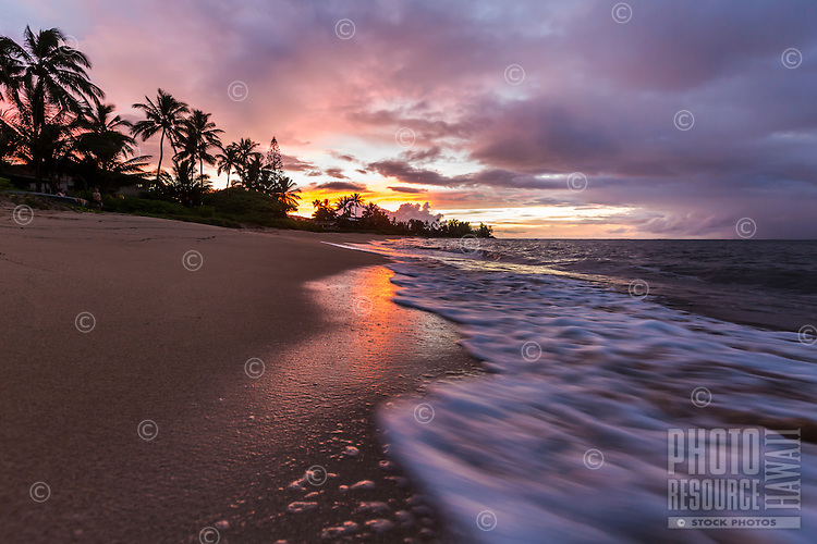 An orange and purple sunset at a beach in Waialua, North Shore, O'ahu.