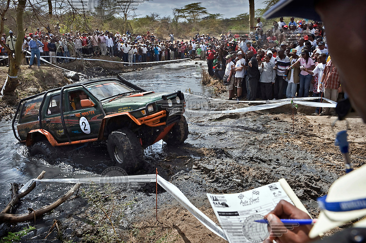 A spectator makes notes as a Toyota Surf, in action during a 4x4 Trail Challenge motor sport event at Athi River, powers its way through a muddy stream.