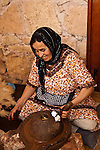 A woman with a toothy smile is grinding the almond shaped nut of the argan tree to extract the oil.