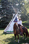 A cowboy in front of a Native American Indian tipi