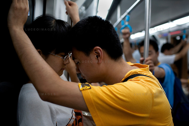 A couple share a moment on the subway in Beijing, China on Tuesday, August 19, 2008.  Kevin German