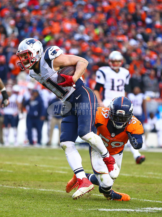 Jan 24, 2016; Denver, CO, USA; New England Patriots wide receiver Julian Edelman (11) is tackled by Denver Broncos linebacker Danny Trevathan (59) in the AFC Championship football game at Sports Authority Field at Mile High. Mandatory Credit: Mark J. Rebilas-USA TODAY Sports