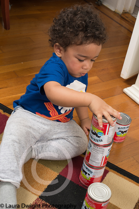 18 month old toddler boy stacking cans, making tower of cans