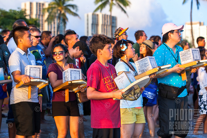 On Memorial Day, participants hold lanterns at the 15th Annual Lantern Floating Ceremony at Ala Moana Beach Park, Honolulu, O'ahu.