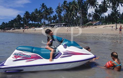 Itaparica Island, Bahia, Brazil. Children playing on a Jetski by the beach at Mar Grande.
