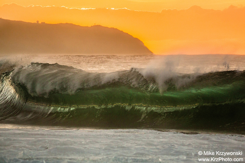 Glowing green breaking wave backed by an orange sky above Kaena Point during sunset, Ke'iki Beach, North Shore, Oahu