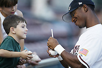 Marcus Nettles of the Lake Elsinore Storm signs a ball for a young fan before a California League 2002 season game at The Diamond, in Lake Elsinore, California. (Larry Goren/Four Seam Images)