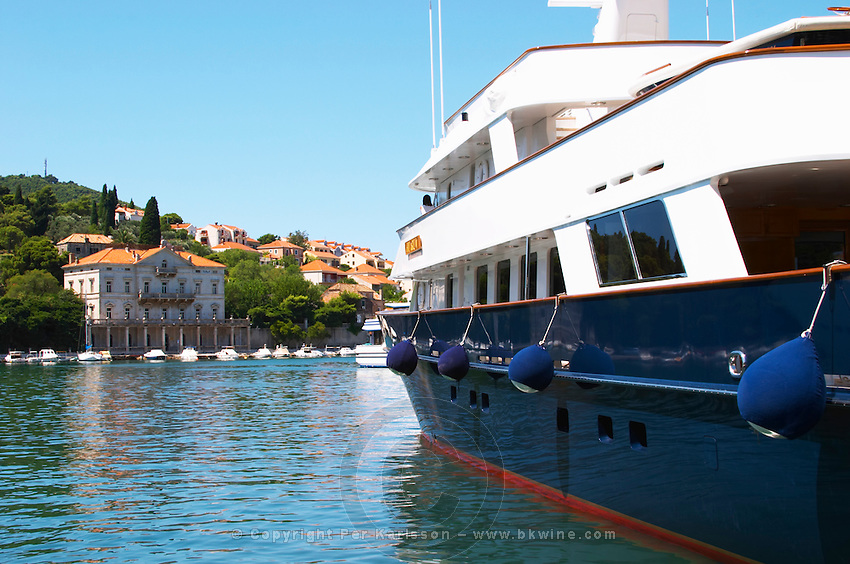 A very big luxurious pleasure motor boat yacht ship, blue and white, American registered with flag, with villas in the background, moored at the dock key. Luka Gruz harbour. Babin Kuk peninsula. Dubrovnik, new city. Dalmatian Coast, Croatia, Europe.