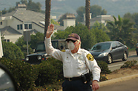 A San Diego Sheriff Senior Patrol Volunteer directs traffic in the Del Mar region of San Diego  Monday, October 22nd 2007. Traffic was heavy as many families with horses and other livestock sought shelter from the wildfires burning in the region at the Del Mar race track.  The San Diego Sheriff's Senior Patrol is comprised of volunteers of age 55 and older who work under the direct supervision of San Diego Sheriff's Department to assist wherever they are needed.