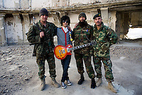 Sulyman Qardash, singer/guitarist in rock band Kabul Dreams poses for a picture with ANA (Afghan National Army) soldiers in the ruins of a castle in Kabul. Kabul Dreams is also made up of bass player Siddique Ahmad and drummer Mujtaba Habibi, and they claim to be the country's first and only rock and roll group.