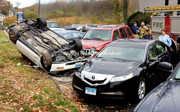 WATERBURY CT. 01 October 2013-110113SV10-A driver lost control in a curve and landed upside down on cars in a medical office building at 1389 West Main St. in Waterbury Friday. The driver suffered minor injuries.<br /> Steven Valenti Republican-American