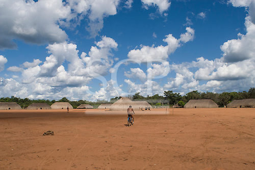 Xingu Indigenous Park, Mato Grosso State, Brazil. Aldeia Waura. Village of traditional oca houses. A man cycles into the village.
