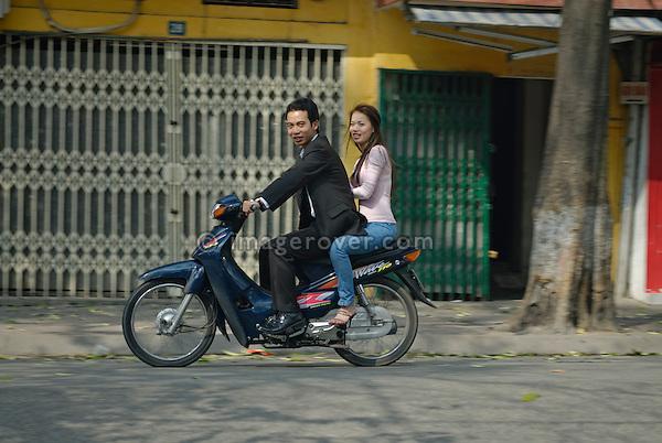 Asia, Vietnam, Hanoi. Hanoi old quarter. Smiling young vietnamese couple riding on small motorbike through Hanoi.