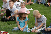 Siblings Holly, 8, and Austin,12, Lenssen of Lynden sit on the Fair lawn during a performance of Valentine's Performing Pigs.  ..