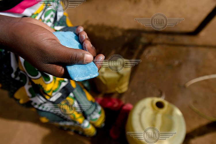 A bar of soap is seen in Catherine Apoyo's hand as she does the washing up at her home.