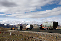 Trucks roll down the Friendship Highway between Lhasa and Nepal.<br /> China started building a controversial 67-mile &quot;paved highway fenced with undulating guardrails&quot; to Mount Qomolangma, known in the west as Mount Everest, to help facilitate next year's Olympic Games torch relay. <br /> Tibet, China.<br /> July, 2007