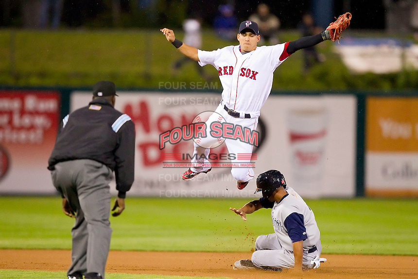 Shortstop Jose Iglesias #10 of the Pawtucket Red Sox leaps for a high throw as Lastings Milledge #14 of the Charlotte Knights slides into second base at McCoy Stadium on June 14, 2011 in Pawtucket, Rhode Island.  The Knights defeated the Red Sox 4-2 in 11 innings.    Photo by Brian Westerholt / Four Seam Images