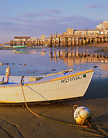 Cape Cod National Seashore, MA<br /> Morning sun on wet tide flats and stranded skiff at low tide, west end wharfs of Provincetown harbor in the distance