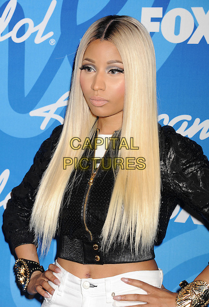 "Nicki Minaj.in the press room at FOX's ""American Idol"" Grand Finale at Nokia Theatre L.A. Live in Los Angeles, California, USA, May 16, 2013..half length black jacket cropped crop midriff white jeans hands on hips gold cuffs bracelet  make-up hair dyed roots wig .CAP/ROT/TM.©Tony Michaels/Roth Stock/Capital Pictures"