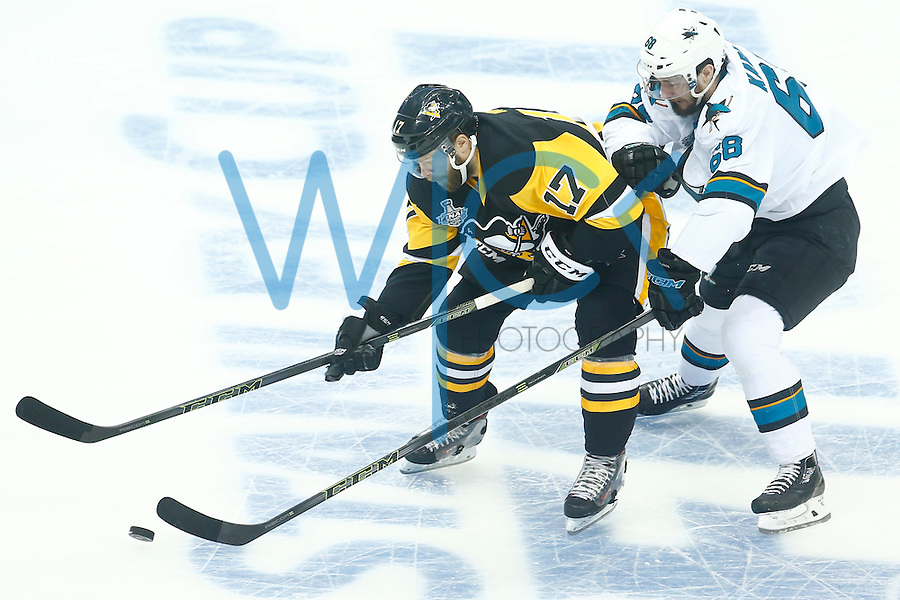 Bryan Rust #17 of the Pittsburgh Penguins reaches for a loose puck in front of Melker Karlsson #68 of the San Jose Sharks in the first period during game two of the Stanley Cup Final at Consol Energy Center in Pittsburgh, Pennslyvania on June 1, 2016. (Photo by Jared Wickerham / DKPS)