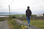 Model released young boy walking on wall along country lane, west coast of Ireland, County Clare, near Ballyvaughan