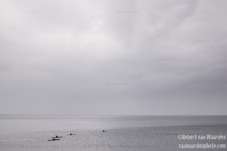Kayakers in the water off the Isle of Skye in Scotland.