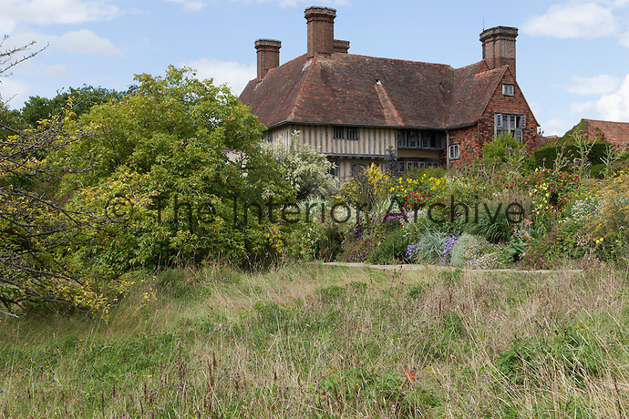 View from the orchard at Great Dixter with the 15th century house behind and Long Border