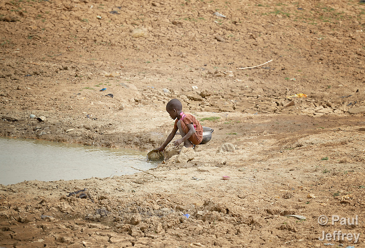 A boy collects water from a muddy pond in Toya, a village in northern Mali near Timbuktu. The region was seized by Islamist fighters in 2012 and then liberated by French and Malian soldiers in early 2013. The Sahel region has been affected by a food crisis for years, often exacerbated by severe droughts.