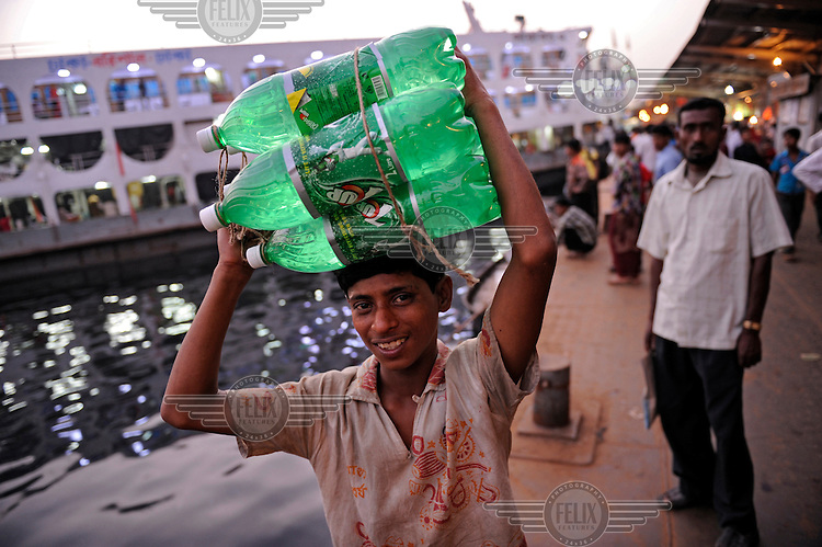 A young man carries 7-Up bottles through the harbour area.