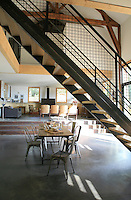 A staircase constructed from steel and wood with wire mesh banisters leads to the upper floors and also serves  as a room divider