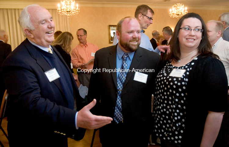 TORRINGTON CT. 28 April 2014-042817SV12-From left, Michael McGuffie, owner of American Bark Mulch &amp; Playground Surfacing, greets guests with his son Nicholas McGuffie and daughter-in-law Laura McGuffie during the Northwest Chamber Annual Meeting in Torrington Monday. McGuffie was inducted into the Chamber Hall of Fame.<br /> Steven Valenti Republican-American