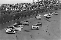 BROOKLYN, MI - AUGUST 11: Darrell Waltrip, driver of the #11 Junior Johnson Chevrolet, leads the field into Turn 1 during the Champion Spark Plug 400 NASCAR Winston Cup race at the Michigan International Speedway near Brooklyn, Michigan, on August 11, 1985.