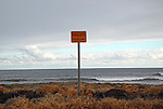 A lonely warning sign at the ocean's edge