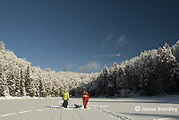 Young girls pulling ice fishing sleds across a frozen lake