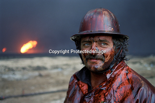 An unidentified fire fighter from Canada stands next to a burning oil fire on August 8, 1991 at Greater Burhan oilfield in Kuwait. When the Gulf War ended in February 1991,the Iraqi forces retreated and hundreds of wells were blown up. Expert teams mainly from USA and Canada arrived and the last fires were put out in October 1991. (Photo by: Per-Anders Pettersson)