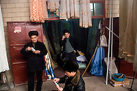 Uighur curtain sellers count money outside of a shop in a textile market in Kashgar, Xinjiang, China.