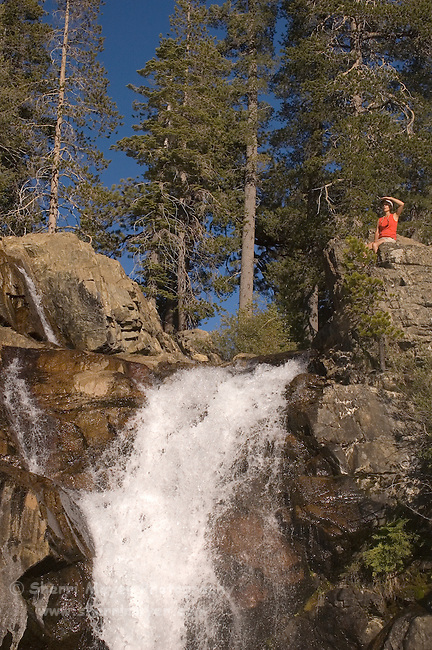Female hiker exploring at the top of a waterfall on Canyon Creek, Tahoe National Forest California