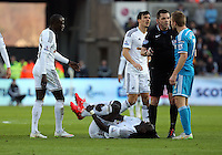 SWANSEA, WALES - FEBRUARY 07: Bafetimbi Gomis of Swansea lies on the ground injured, while Sebastian Larsson of Sunderland (R) is spoken to by match referee Phil Dowd during the Premier League match between Swansea City and Sunderland AFC at Liberty Stadium on February 7, 2015 in Swansea, Wales.