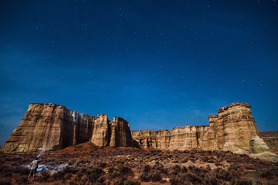 An adult male scans the sandstone cliff formations commonly referred to as the Pillars of Rome with a headlamp at night in Southeast Oregon.