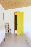 An acid yellow door adds a touch of colour to this all-white bedroom