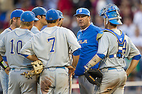 UCLA head coach John Savage meets with his team on the mound during Game 1 of the 2013 Men's College World Series Finals against the Mississippi State Bulldogs on June 24, 2013 at TD Ameritrade Park in Omaha, Nebraska. The Bruins defeated the Bulldogs 3-1, taking a 1-0 lead in the best of 3 series. (Andrew Woolley/Four Seam Images)