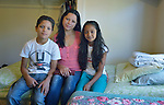 Dayanara Lopez and her children Josue Isaac and Genesis pose in a shelter in San Antonio, Texas, on December 2, 2015. Lopez and her children, along with two teenage nephews, fled Honduras in October 2015 because of domestic violence and threats and assaults against her nephews from gangs. After requesting political asylum in the United States, they were held for several days by immigration officials and then released. The nephews were turned over to their mother, who already lived in the U.S. Lopez and her children stayed at first in the shelter, which is run by the Refugee and Immigrant Center for Education and Legal Services (RAICES) and supported by a coalition of San Antonio churches. They then traveled by bus to another location in the U.S. while they await a final decision on their asylum petition. In the photo, Lopez holds a Bible which she brought on the journey to the U.S.