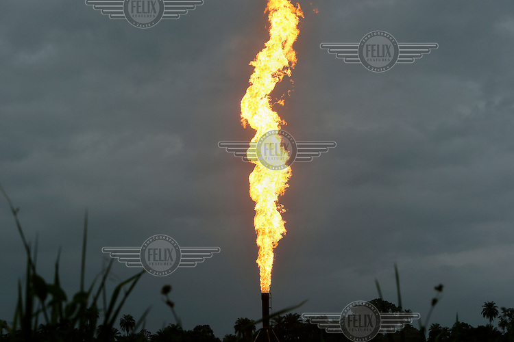 The Oshie gas flare, which occassionally spurts a jet of flaming liquids. The flare belongs to the Agip oil company and has been burning continuously since 1972. <br /> The Rumuekpe community suffered much damage during the conflict among various rival militants and cult gangs over access to oil money. The inter-communal violence killed so many people, including women and children, between 2005-08. Thousands more were displaced by fighting that left homes, schools and churches in ruins with many suffering poverty and homelessness.