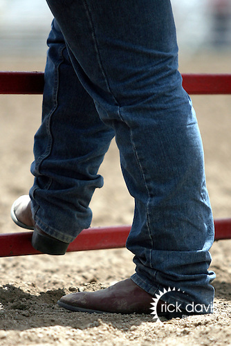 A cowboy takes a break along the fence between rodeo action at the annual Cheyenne Frontier Days Rodeo in Cheyenne, Wyoming.