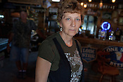 """KARNES COUNTY, TX - SEPTEMBER 25, 2013: Portrait of Lynn Buehring, and her husband Shelby in the background,  in Shelby's """"man cave"""" at their home near Karnes City, Texas. CREDIT: Lance Rosenfield/Prime"""