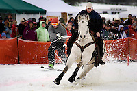 Competitors race during the Whitefish Skijoring World Championship event in Whitefish, Montana, USA.  Skijoring is a competitive sport in which a person on skis navigates an obstacle course while being pulled behind a galloping horse.